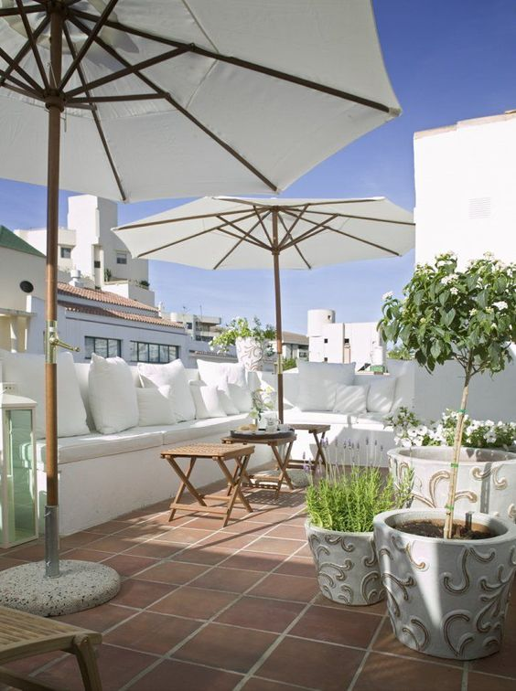 a white summer terrace with a built-in bench, white pillows, pottted blooms and greenery and umbrellas