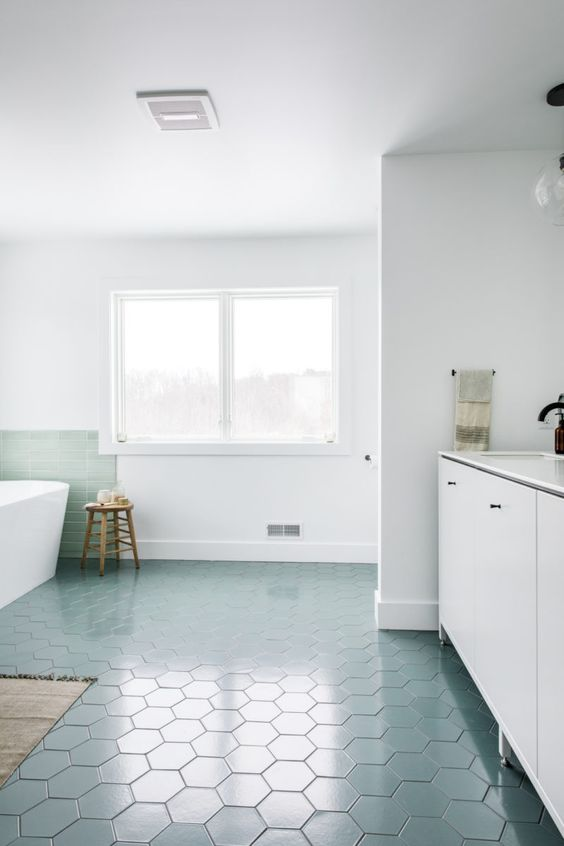 an airy and serene bathroom with blue hex tiles on the floor and a mint backsplash, white furniture and white appliances