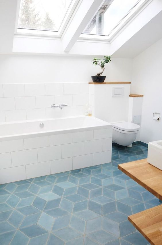 an airy attic bathroom with blue geometric tile floor, large scale subway tiles and white appliances