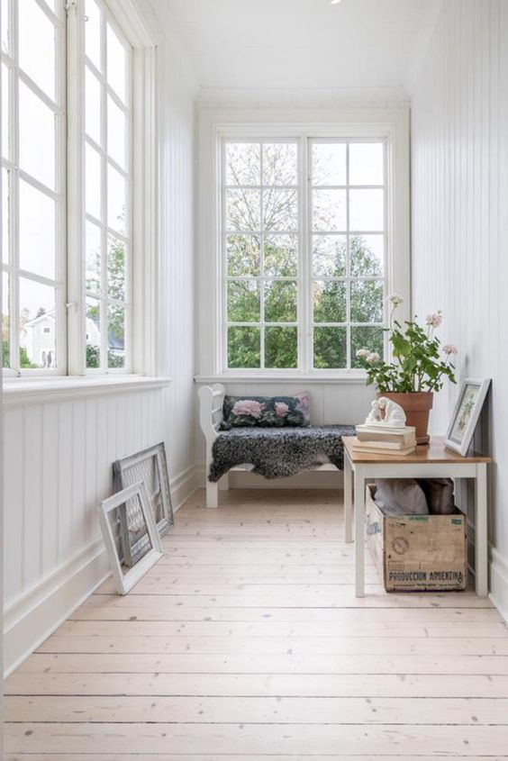 an airy small sunroom with a bench, a table with a crate and some artworks is a welcoming space