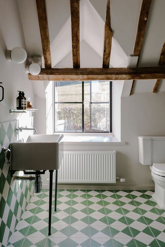 an attic farmhouse bathroom with white and green geo tiles, a free-standing sink and white appliances and wooden beams