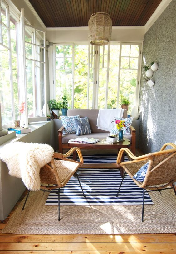 an eclectic and boho sunroom with wicker chairs and lamps, with layered rugs and touches of color