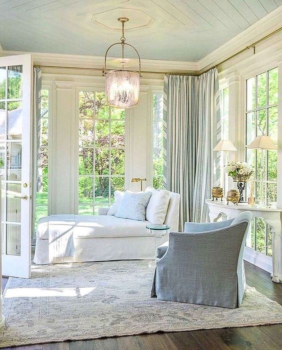 an elegant vintage sunroom with a white daybed and a light blue chair, a vintage table with lamps and a cool pendant lamp