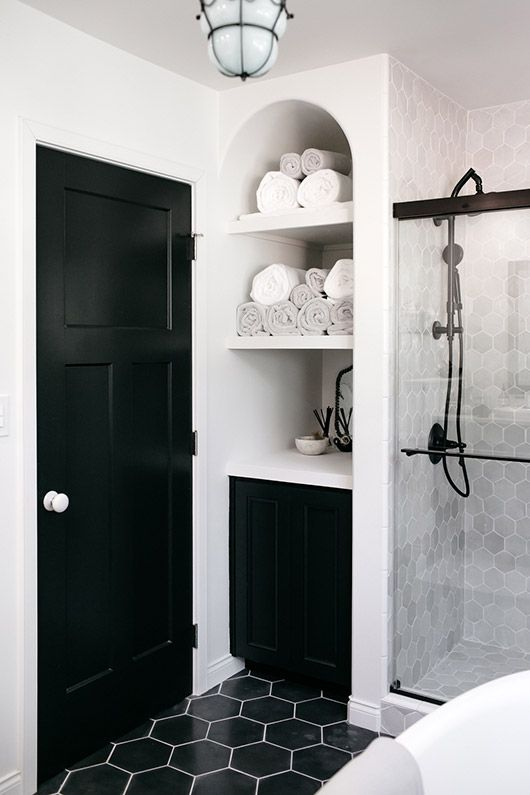 an eye-catchy bathroom with grey marble and black hex tiles, white appliances and textiles and black fixtures for a more modern feel