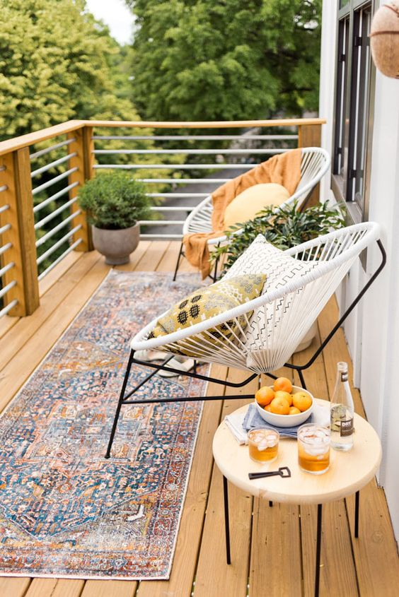 an inviting summer balcony with a boho rug, some round chairs, a table and potted greenery plus pillows