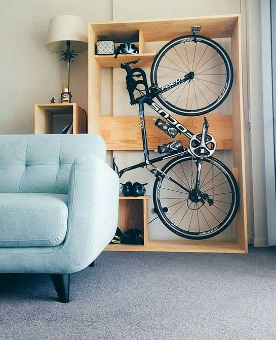 an open plywood storage unit with a bike and various stuff stored is a cool idea for a modern space and this unit can be placed even in a living room
