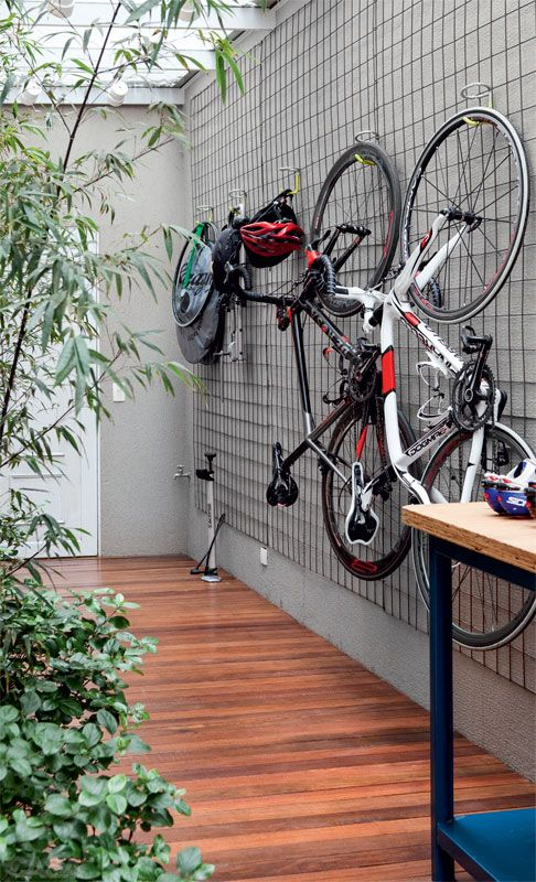 an outdoor space with a grid on the wall and bikes attached to the grid is a very cool and fresh idea to store them outdoors
