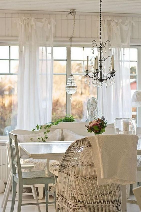 a beautiful vintage cottage sunroom in white, with wooden and wicker furniture, a crystal chandelier and greenery