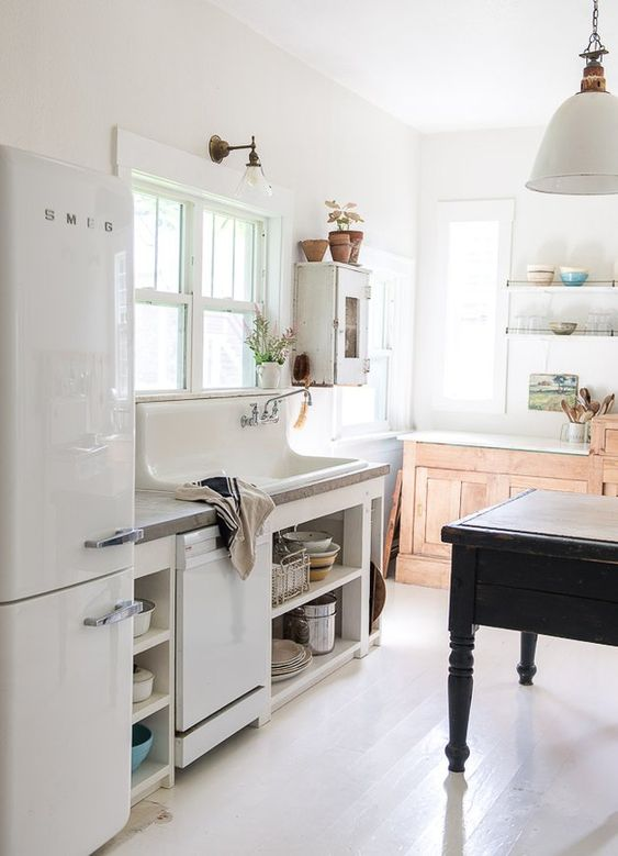 a beautiful vintage kitchen with white and stained cabinets, a black vintage table as a kitchen island, potted plants and pendant lamps and sconces