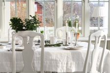 a beautiful vintage sunroom in white, vintage furniture, a crystal chandelier, candles and potted plants