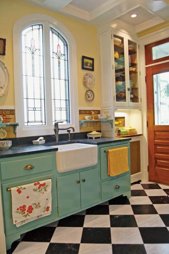 a bright retro kitchen with a checked floor, yellow walls, blue cabinetry, black countertops, vintage faucets and bright textiles