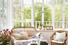 a bright vintage sunroom with a colorful rug, wicker furniture and floral pillows, a potted plant and a mini table
