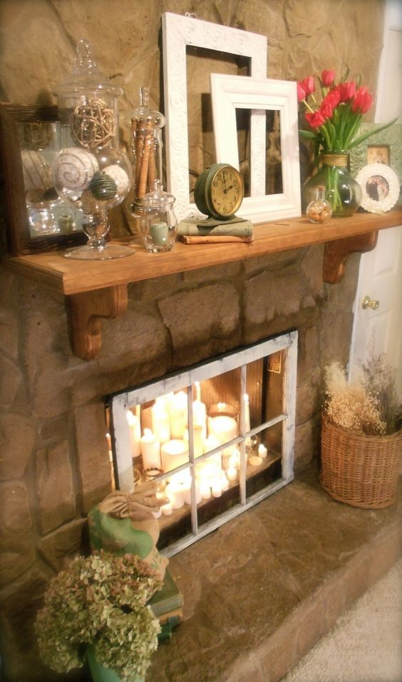 a candle arrangement of different candles placed in the fireplace and a vintage window covering it