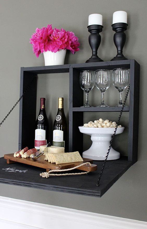 a chalkboard foldable wall mounted bar with candles, wine, glasses and various appetizers