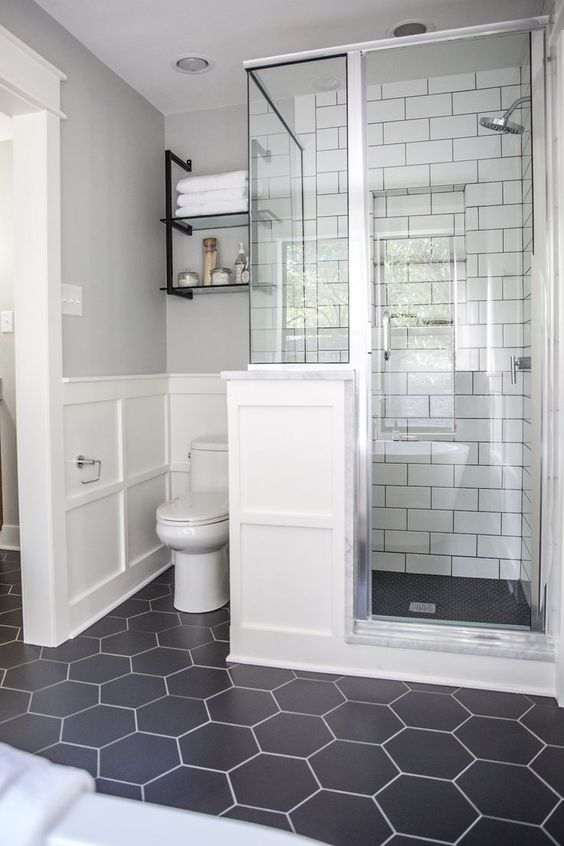 a chic bathroom with a black hex tiles floor, white subway tiles in the shower space and white paneling on the wall