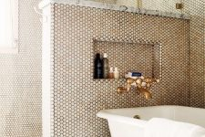 a chic bathroom with grey tiles and penny ones on the walls, a pony wall, brass touches and a vintage bathtub