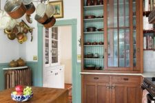 a chic vintage kitchen with mint green paneling, stained vintage furniture, a foldign table as a kitchen island, a hanger with pans