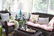 a chic vintage sunroom with dark rattan furniture, colorful textiles, a bright artwork and a blue table lamp