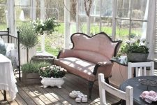 a chic vintage sunroom with neutral forged and wooden furniture, a pink sofa, potted blooms and much sunlight
