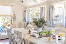 a chic vintage to shabby chic sunroom with white shabby furniture, striped curtains, greenery and a rustic lamp