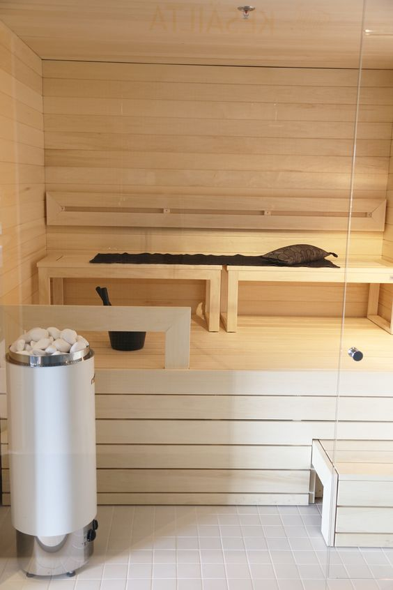 a chic whitewashed wooden sauna with several benches and just some light is welcoming