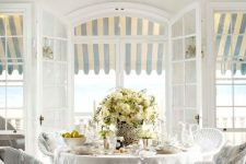 a classic vintage sunroom done in all-neutrals, with a white wicker furniture set, potted blooms and neutral textiles