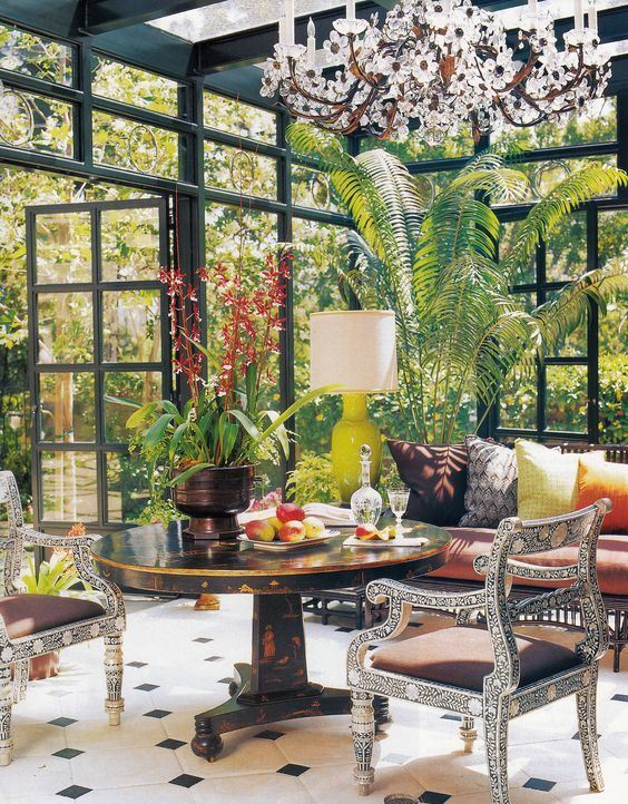 a colorful vintage sunroom with a dark stained table, refined chairs, a daybed with vibrant pillows, potted greenery and a gorgeous floral chandelier