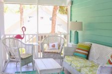 a colorful vintage sunroom with white wicker furniture, printed textiles, a pink flamingo and a blue lamp