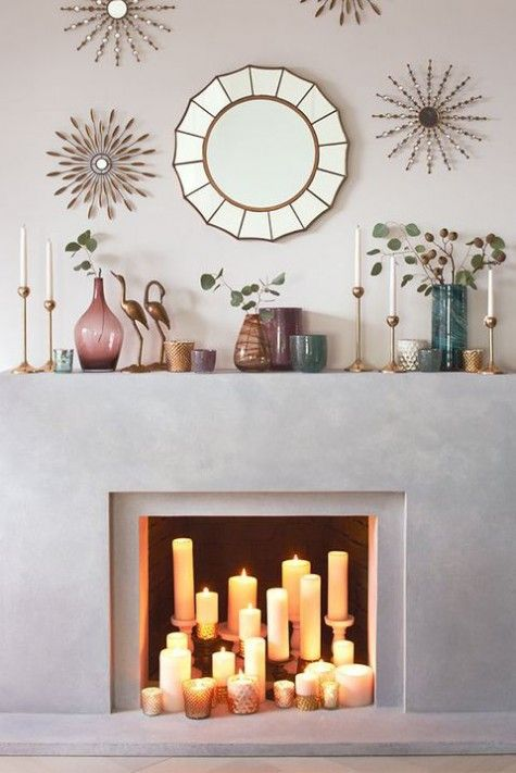 a concrete fireplace with pillar candles in candle holders and mercury glass votives plus colored glass vases on the mantel