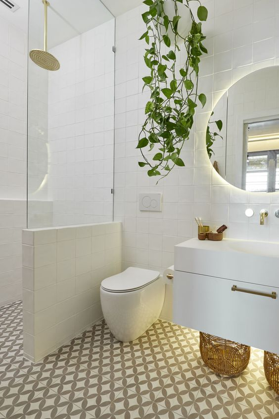 a contemporary bathroom clad with mosaic tiles, with a floating vanity, a half wall with glass to separate the shower space and a potted plant