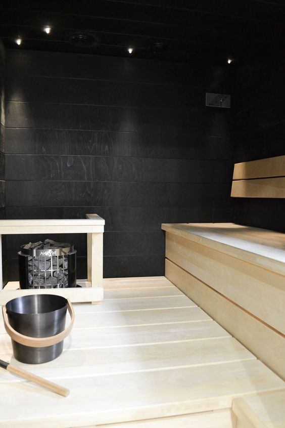 a contrasting black and white steam room with black walls and light stained wooden furniture is cool