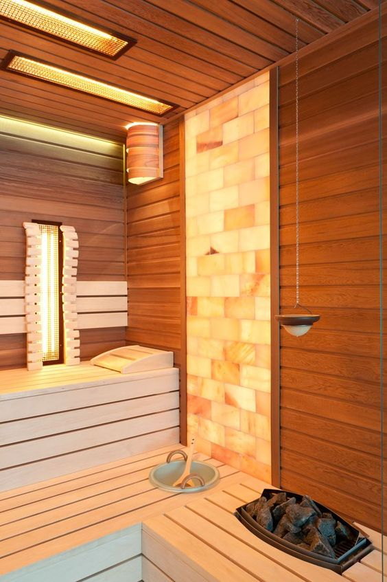 a cool steam room clad with wood and with a mosaic tile part, with some built-in lights is bold and cozy