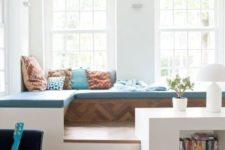 a cozy sitting space on a platform with a storage unit with niches is fully separated from the rest of the space