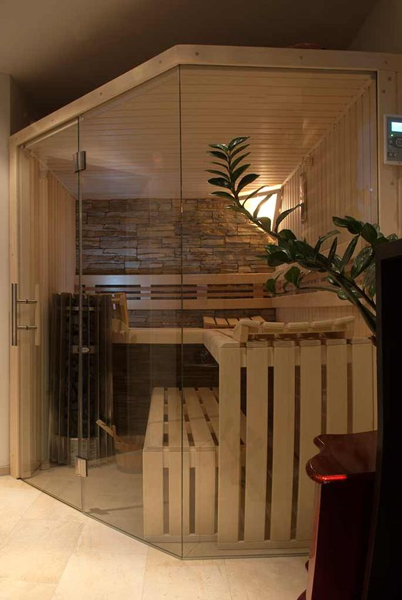 a cozy tine home sauna with wooden benches, a stone accent wall and some intimate light plus a glass wall