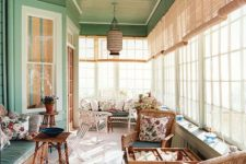 a cozy vintage sunroom in green and neutrals, wicker and wooden furniture, floral textiles, a pendant lamp and lots of sunlight