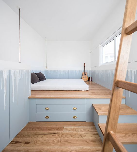 a custom-designed wooden platform with steps and drawers for storage saves much space in a tiny bedroom
