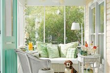 a cute neutral vintage sunroom with a mint ceiling, white wicker furniture, printed pillows and a minty door