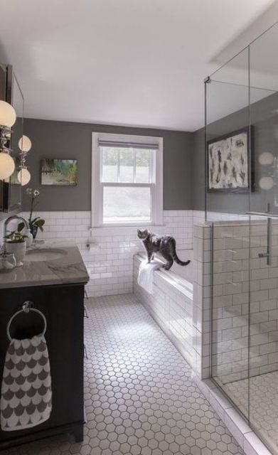a farmhouse bathroom with white subway tiles and hex ones, with grey walls, a shower space with a pony wall and a black vanity