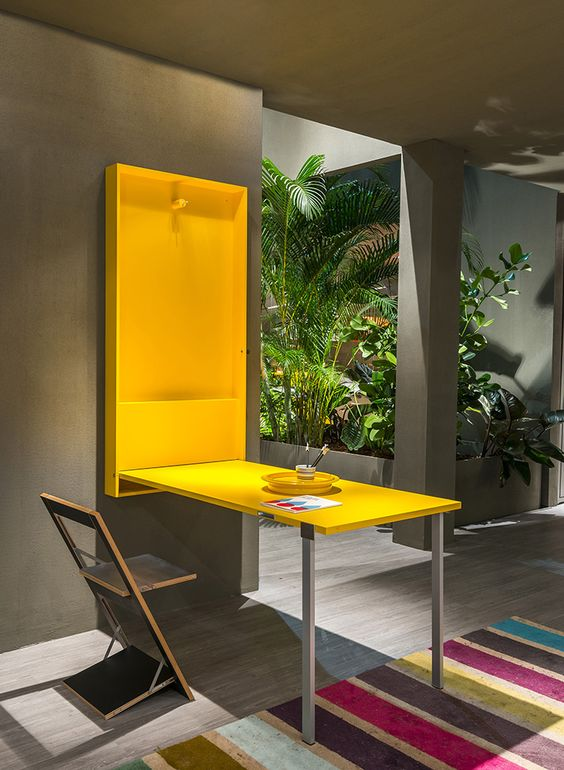 a folding desk or dining table in sunny yellow can be hidden anytime, and the chair is folding too