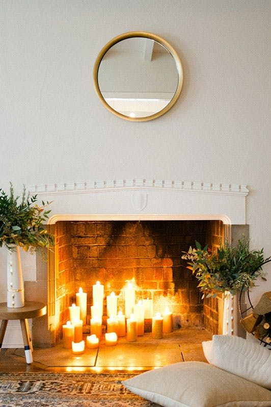 a hygge fireplace with lots of candles and greenery arrangements in beautiful vases for a natural feel