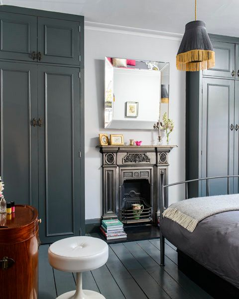 a laconic vintage bedroom in grey and white, with a fireplace, a pendant lamp with fringe and a metal bed