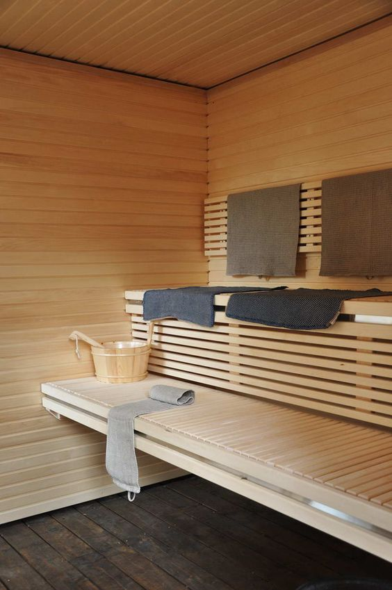 a large welcoming wood clad sauna with two floating benches and some towels is warming up