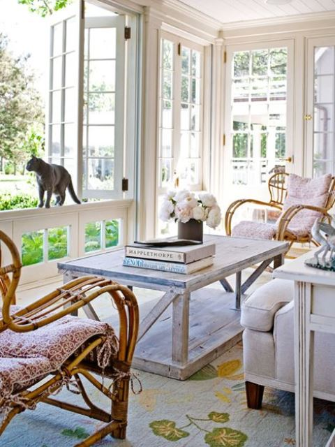 a light vintage sunroom with vintage wooden and rattan furniture, pastel and neutral textiles and blooms