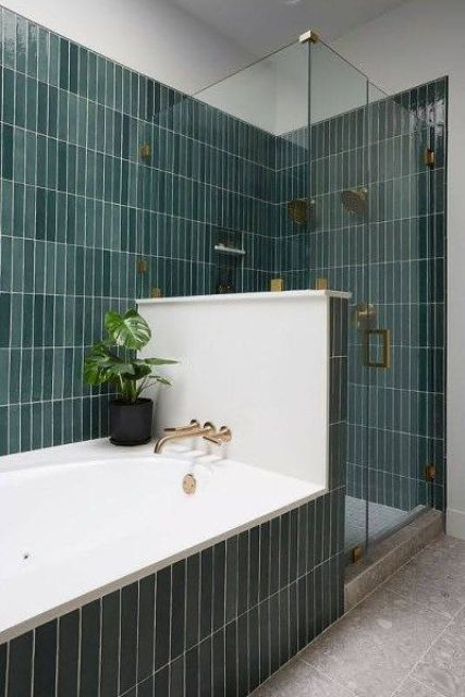 a lovely bathroom clad with green skinny tiles, with a half wall to divide the bathtub and shower space is amazing
