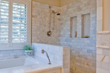 a lovely bathroom clad with marble tiles, with a half wall in the shower space, a bathtub clad with panels