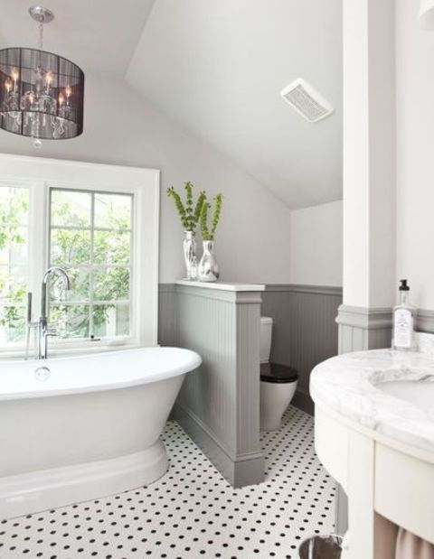 a lovely farmhouse bathroom with a tile floor, grey paneling on the walls, a vintage tub and a chic chandelier plus a half wall that separates the space