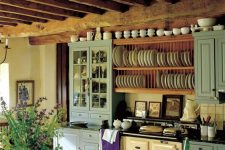a lovely vintage kitchen with blue cabinets, a vintage hearth, open shelves for plates, wooden beams and a wooden dining set