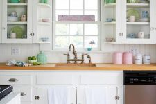 a lovely vintage kitchen with white cabinets, a white beadboard kitchen island,pink, blue and green accessories and neutral linens