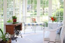 a lovely vintage sunroom with wooden and forged furniture, printed upholstery, potted greenery and blooms