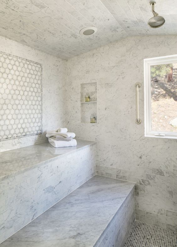 a luxurious white marble tile steam room with two long benches, niches and a window to enjoy the views